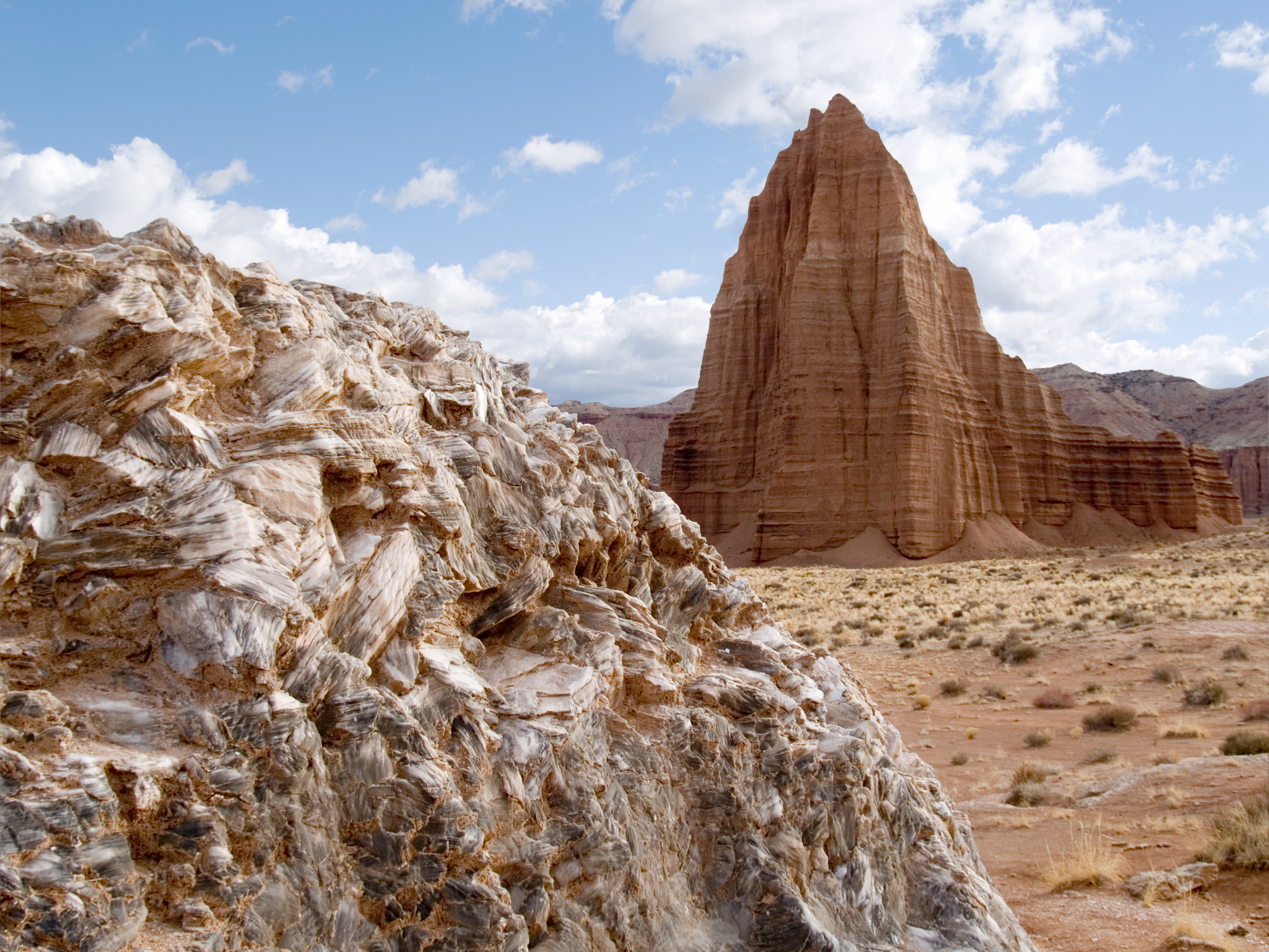 "Two of Capitol Reef National Park's popular attractions: Glass Mountain (foreground) and Temple of the Sun (background). Glass Mountain is a large exposed mound of selenite gypsum that formed within the Jurassic-aged Entrada Sandstone. The ""gypsum plug"" became exposed as the relatively soft Entrada Sandstone eroded away. Temple of the Sun is a large monolith that was also created by erosion of the Entrada Sandstone. Temple of the Sun, Capitol Reef National Park, Wayne County, Utah Photographer: Michael Vanden Berg"