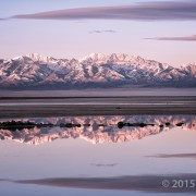 Alpenglow illuminates the glacially sculpted Stansbury Mountains as seen from the shores of Great Salt Lake. Deseret Peak (11,031 feet), the leftmost high summit, is the range's highest peak and is underlain by Cambrian-age Prospect Mountain Quartzite. Stansbury Mountains, Tooele County, Utah Photographer: Gregg Beukelman; © 2015
