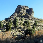 "Step Mountain is a Tertiary-aged (dated at 36 million years) andesitic dike in Rose Canyon, three miles southwest of Herriman. The summit is at 6109 feet above sea level. The mountain is a fine example of columnar jointing, typically associated with basalt, but also found in andesites. Columnar jointing is found below the surface of thick lava flows, sills, and dikes, and is caused by the cooling and contracting of the lava creating long vertical joints that form slender polygonal columns, typically pentagonal or hexagonal in shape. In the case of Step Mountain dike, magma filled a crack in the pre-existing rock and the joints formed horizontal to the surface, so the columns act as ""steps."" The weathering-resistant dike now has a prominent relief due to the erosion of the softer surrounding volcanic rock."