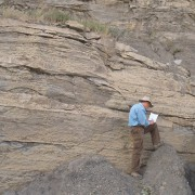 UGS Energy & Minerals geologist examining rock outcrop.