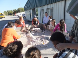 Students learning about erosion and deposition at the stream trailer during Earth Science Week.