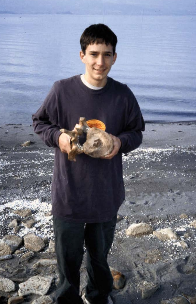 Tobin Warner on the shore of Bear Lake with the mammoth vertebra he discovered.