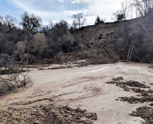 With constant spring flow, the landslide deposit erodes and the redeposited sediment forms a smooth alluvial fan on the property at the base of the bluff. Photo date March 20, 2018.